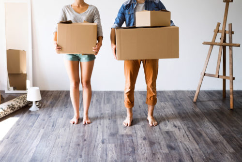 unrecognizable-couple-with-boxes-moving-in-new-hou-P5T35FV